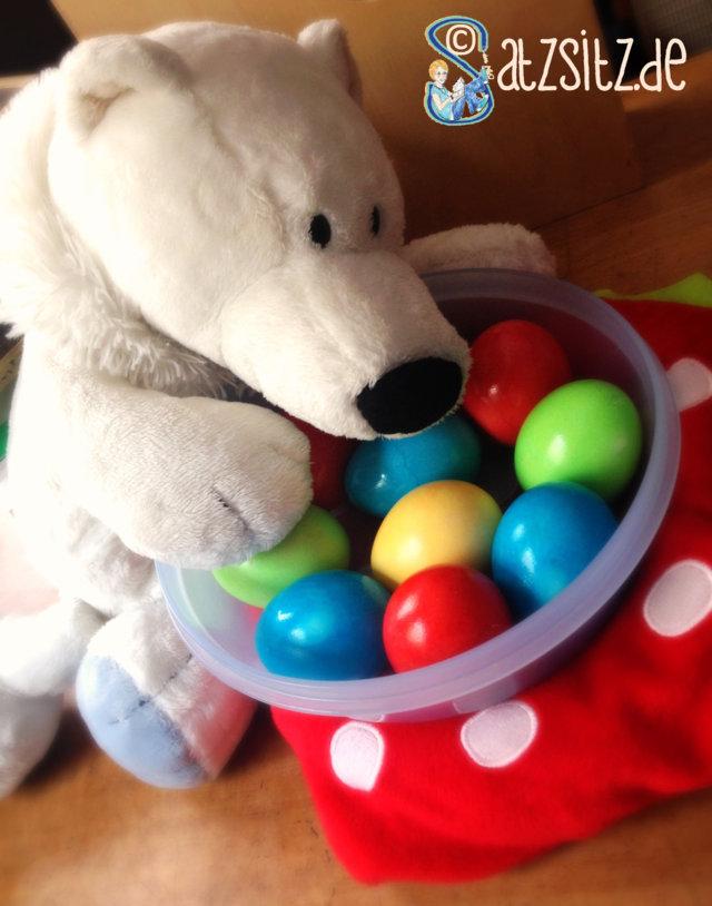 Poldi findet eine Schüssel bunter Ostereier. Sie stehen auf einem Erdbeer-Kissen.